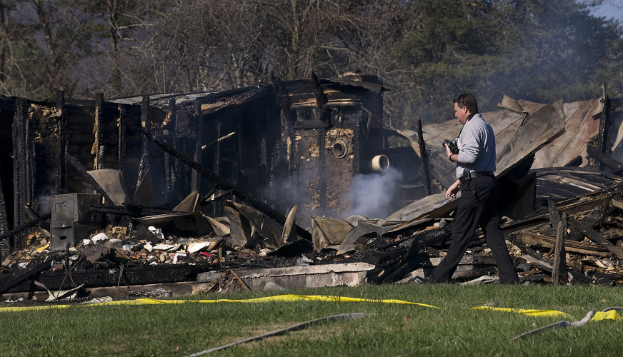 Shenandoah County Fire Marshal Dave Ferguson walks past a home at 105 Millertown Road west of Edinburg on Monday that was destroyed by fire on Sunday night.   Rich Cooley/Daily